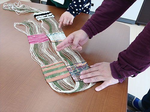 織りあがったコースターを持ったKさんの写真です。