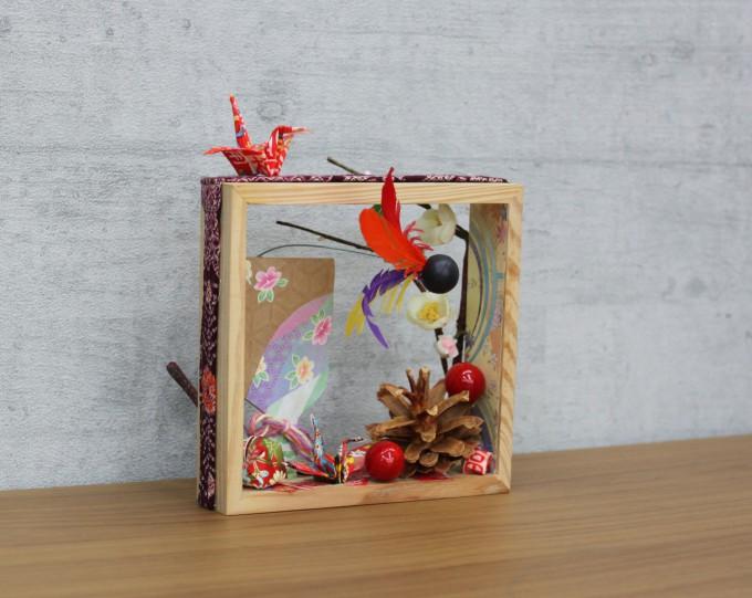 立体作品の写真。四角い枠の中に、お正月の飾りがコラージュされています。
