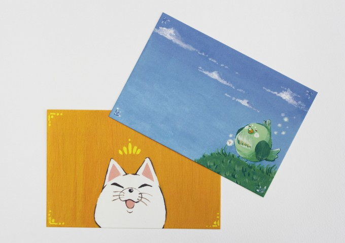 絵葉書2枚の写真。黄色い背景に猫が描かれたイラストと、空色の背景に鳥が描かれたイラストが印刷されています。