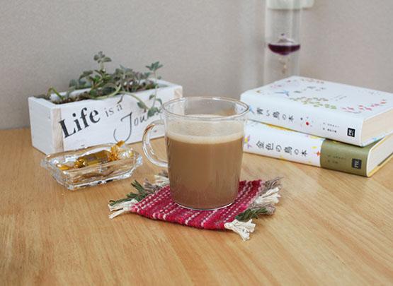 コースターにコーヒーカップをのせている写真。